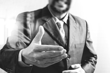 businessman with an open hand ready to seal business investor project deal,front view,black and white