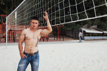 muscular male model with perfect body posing in blue jeans
