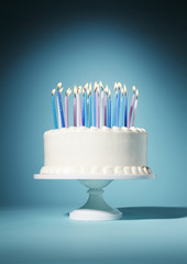 White birthday cake with lit candles