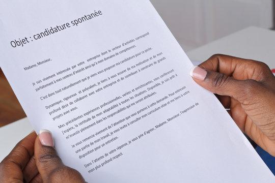 main femme noire lisant une lettre de candidature spontanée