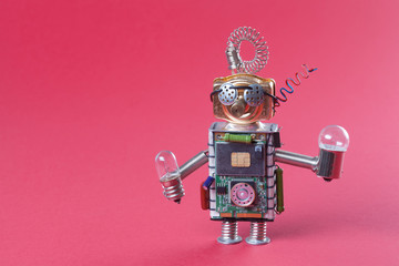 Robot concept retro style. Circuits socket chip toy mechanism, funny head, eyes glasses, light bulbs in hands. Copy space, pink background