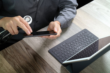 top view of medical doctor hand working with smart phone,digital tablet computer,stethoscope eyeglass,on wooden desk