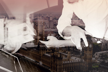 double exposure of hipster hand holding headphone,using digital tablet docking keyboard and mobile payments online business,omni channel,sitting on sofa in living room,London city