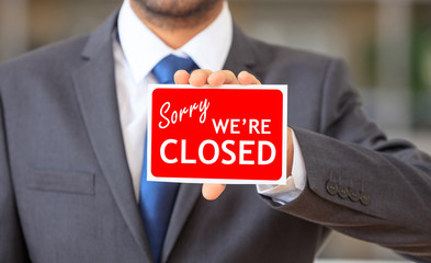 Man holding a sorry we are closed sign