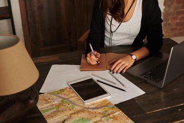 Woman planning new trip. Girl write tourist notes at home. Tablet, laptop, city map on the table. Girl learn the route in the new city. Loft interior with big wooden doors.