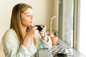 Woman enjoying the smell of coffee