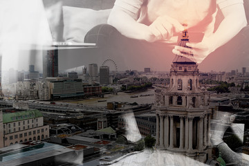 double exposure of hipster hand using digital tablet docking keyboard and smart phone for mobile payments online business,omni channel,sitting on sofa in living room,London architecture city