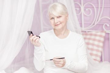 Senior lady doing makeup.
