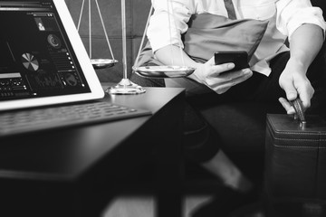 Justice and Law context.Male lawyer hand sitting on sofa and working with smart phone,digital tablet computer docking keyboard with gavel and document on living table at home,black and white