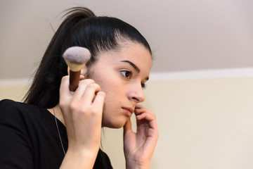 A young teenage girl in front of the makeup mirror