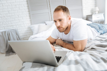 Handsome bearded man surfing the Internet at home