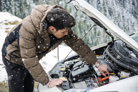 Young man near car with open hood inspecting engine in winter. Snowy forest on background