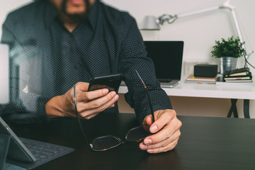 businessman,designer hand using smart phone,laptop,eyeglasses,online banking payment communication network technology 4.0,internet wireless application,modern office,filter effect