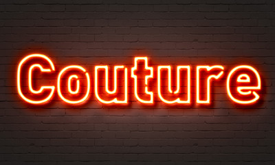 Couture neon sign on brick wall background.