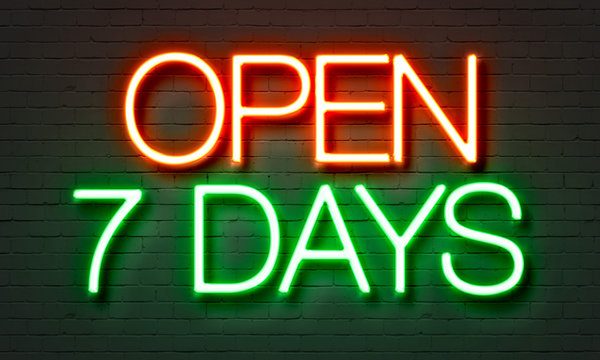 Open 7 days neon sign on brick wall background.