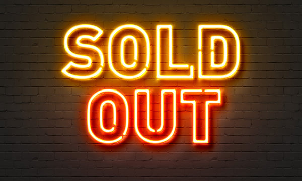 Sold out neon sign on brick wall background.