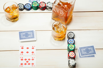 game of poker and a glass  whiskey with ice on  white wooden background