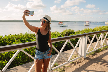 "Woman taking self portrait in tourist spot ""Jacare river beach"", near Joao Pessoa, Brazil"