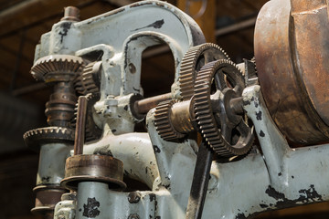 Closeup view of beautiful detailed old vintage machine tool gears and other parts on dark background