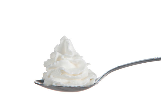 Whipped cream nicely curled on a spoon isolated on white background. Nitrous oxide fuels the expulsion of whipped cream from spray cans, which was recently in short supply due to a factory explosion.