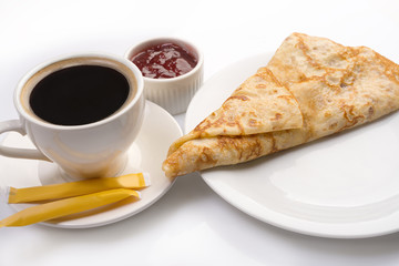 Pancake on plate with cup of black coffee and jam