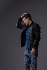 Casual young man in black jacket, jeans and boots on black background. Studio shoot.