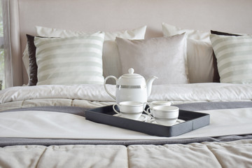 Decorative tray of tea set on the bed in modern bedroom interior