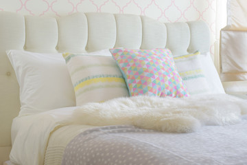 Sweet colorful pillows setting on bed with puffy scarf