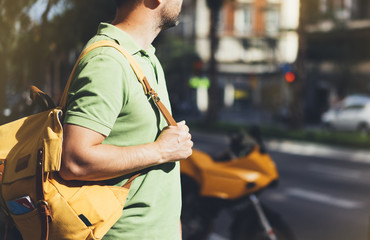 Hipster young man holding in hands backpack and map. Side view tourist traveler planning route on background sun and orange motorcycle. Person visiting the sights city on backdrop summer street