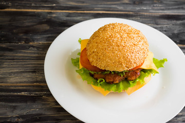 Hamburger on a wooden table in rustic style and ingredients