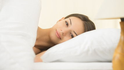 The cute woman lay on the bed with white linens