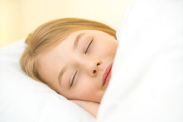 The cute face of the young girl on the pillow