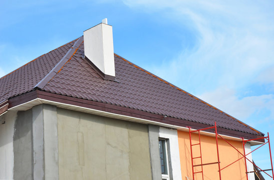 Metal roof construction with chimney installation, stucco, plastering and painting house wall. Metal Roofing Construction with Plastic Soffits.