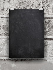 Blank blackboard frame hanged by clips against gray wall
