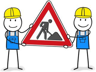 Zwei Figuren heben ein Bauarbeiten / Umbau Schild in die höhe