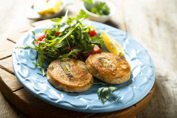 Salmon cakes with vegetables and arugula salad