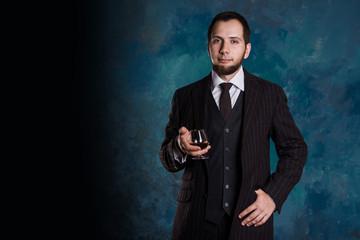 Handsome man sommelier holds cognac glass
