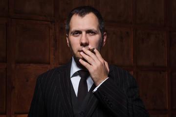 Bearded man smokes in luxury cabinet