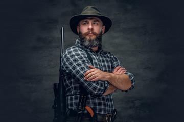 Bearded hunter holds a rifle.