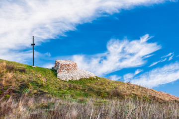 Cross and altar made of stones on top of a mountain, as background a beautiful blue sky