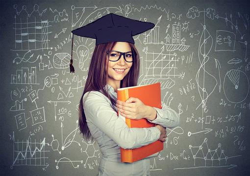 Smart student with graduation cap over math science formulas blackboard