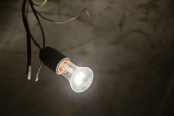 Light bulb close-up in a dark room. Background.