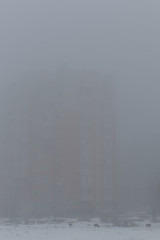 Multi-storey building in the fog. Foggy morning in the winter.