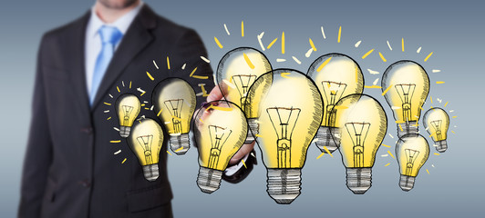 Businessman drawing a lightbulb with a pen