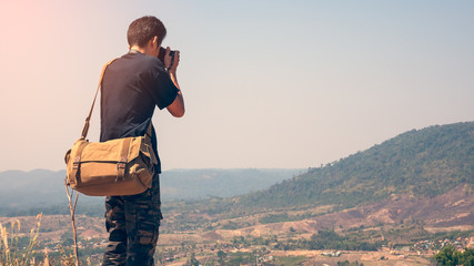 Closeup rear view of a photographer taking pictures on a mountain.