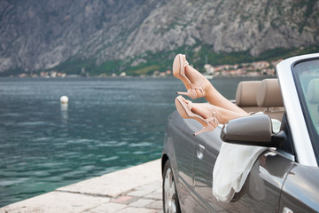 Shoes with high heels are on bride`s legs. Woman sits in metallic cabriolet car on background of beautiful views of mountains and sea.