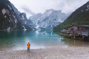 Female hiker standing next to the beautiful mountain lake