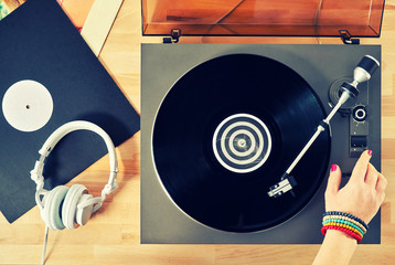 Gramophone with vinyl records and headphones on a wooden table. Hand girl with a bright accessory includes gramophone. Basic background for design