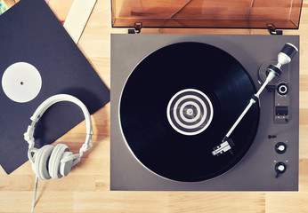Gramophone with vinyl records  on a wooden table. Basic background for design