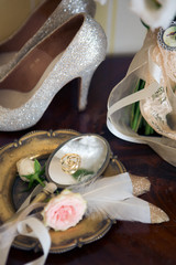 Wedding decoration: shoes, rings and bouquet on a table